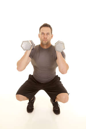 A man doing a squat while lifting weights. photo