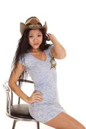 cowgirl hat: Una mujer asi�tica sentada en su taburete con una peque�a sonrisa en el rostro con el sombrero de vaquera en.