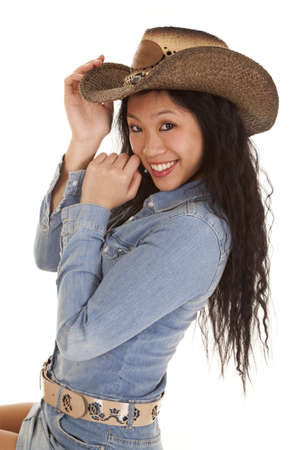 A woman in her cowgirl hat with a big smile on her face. photo