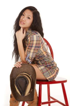 cowgirl hat: Una mujer con su vestido a cuadros sentado en una silla roja se aferra a su sombrero de vaquera. Foto de archivo