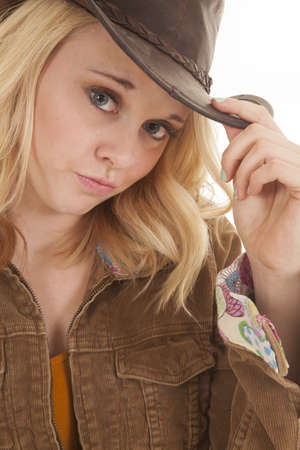 brim: A woman with her hand on the brim of her hat looking.