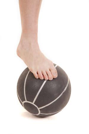 A woman has her foot on a medicine ball. photo