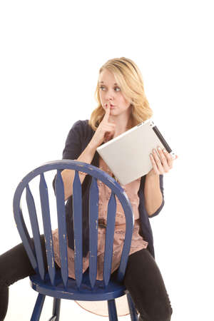 A woman sitting on a chair holding on to her tablet with her finger up to her lips. photo