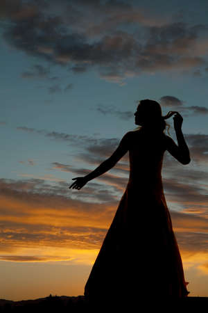 a silhouette of a woman reaching out and playing with her hair. photo