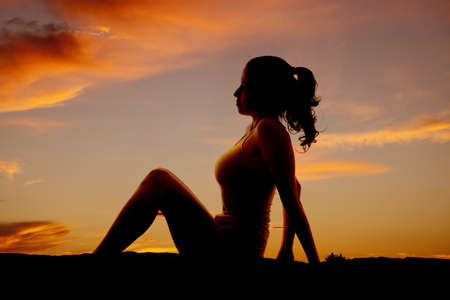 knees up: A woman is sitting in the sunset with her knees up.