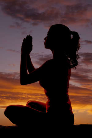 shadow: A woman is sitting in a yoga pose silhouetted in the sunset. Stock Photo