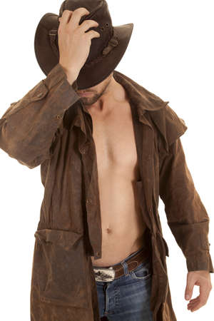 a man holding on to his western hat in his duster without a shirt.