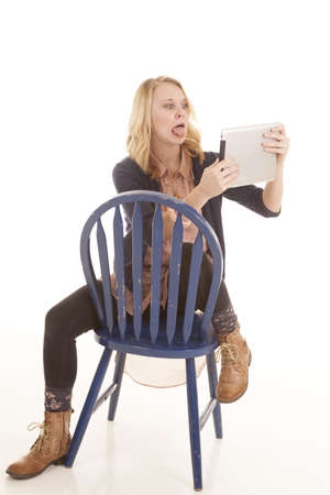 a woma making a funny face on her electronic tablet while sitting in a blue chair. photo