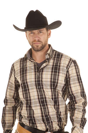 A cowboy showing his serious side with his plaid shirt and black hat on. Stock Photo