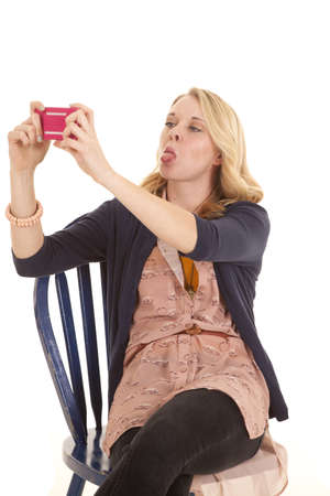 a woman sitting in her chair taking a picture of herself with her cell phone, while she sticks out her tongue. photo
