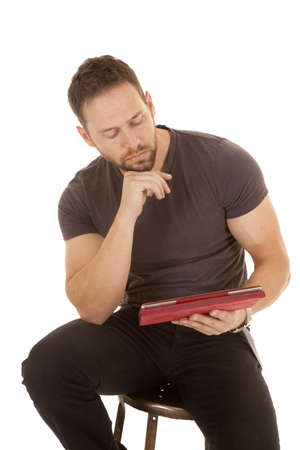 a man sitting on a stool looking at his tablet studying . photo