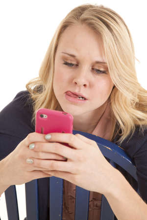 A woman thinking really hard while she is text-ing on her cell phone.