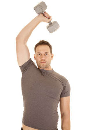 A man working out with a weight over his head working on his tricepts. photo