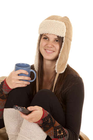 long johns: A woman sitting in her warm clothes drinking a warm drink and watching tv laughing. Stock Photo