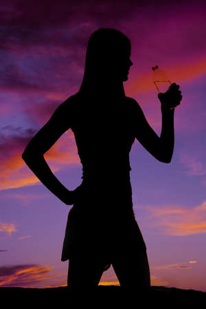 A silhouette of a woman holding  on to her water bottle. photo