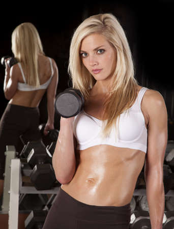 a woman working out in a gym holding on to a weight with a serious expression. photo