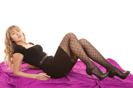 knees up: A woman laying back on a pink sheet with her knees up and heeled shoes on