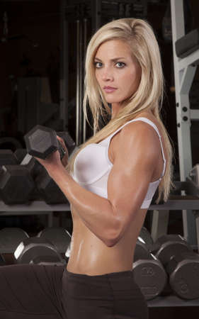 a woman looking and doing arm curls in a gym. photo