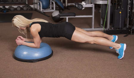a woman doing a plank position in a gym. photo