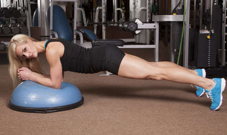 A woman looking while doing plank in a gym on a half ball. photo