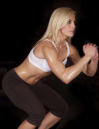A woman with a serious expression doing a squat with sweat all over her body