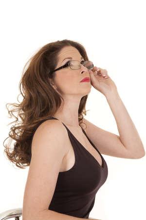 A woman in a black tank top holds her glasses and looks up to the side. photo