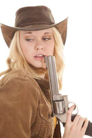 A cowgirl holding on to her weapon up by her mouth looking back. Imagens