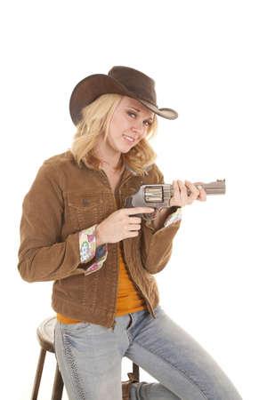 cowgirl hat: una mujer en su sombrero de vaquera que sostiene a su pistola con una sonrisa en los labios.
