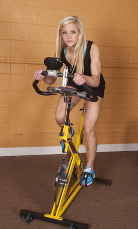 A woman in the gym riding an exercise bike with a serious expression on her face. Stock Photo - 18189801
