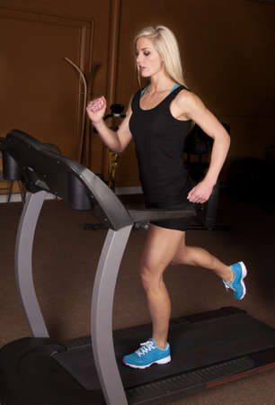 A woman with a serious expression and running on her treadmill. Stock Photo