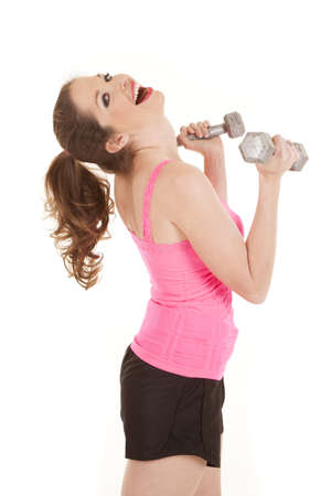 A woman in a pink tank with weights has her head back laughing. photo