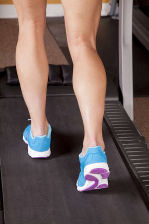 A close up of a woman running a treadmill. photo