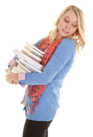 A woman with a stack of books looking down trying not to drop them Stock Photo - 18189415