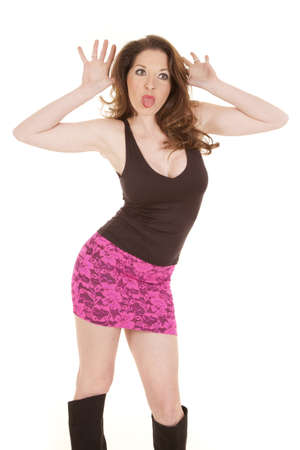 A woman in a hot pink skirt is sticking out her tongue. photo