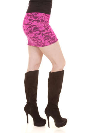A woman in black boots and a pink skirt from the waist down. photo