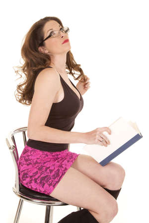 A woman in a pink skirt is reading a book. photo