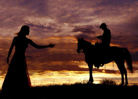 western saddle: A cowboy is sitting on a horse in the sunset swinging a rope. Stock Photo