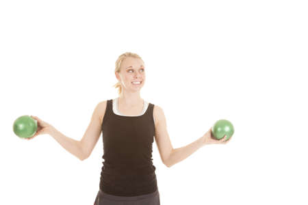 weighted: a woman holding out weighted green balls working out with a smile on her face.