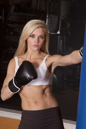 A woman working out in a gym with boxing gloves and punching bag.