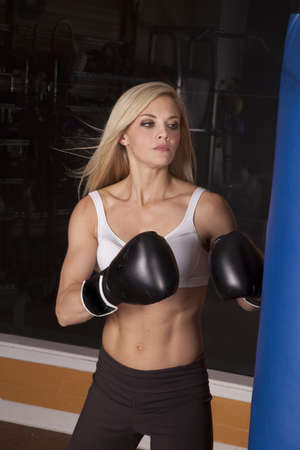 muscle girl: A woman working out in a gym with boxing gloves and punching bag.