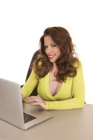 web surfing: A woman with a laptop sitting at a table. Stock Photo