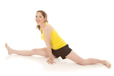 A woman in a yellow tank top doing the splits photo