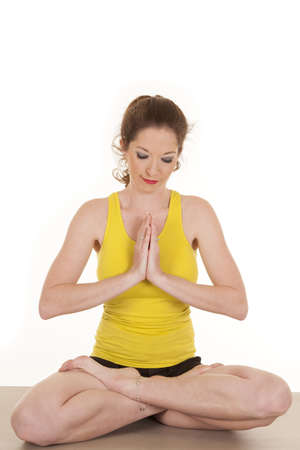 A woman in a yellow tank top in yoga prayer position. photo