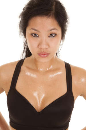 A woman with a serious expression sweating after an intense workout.