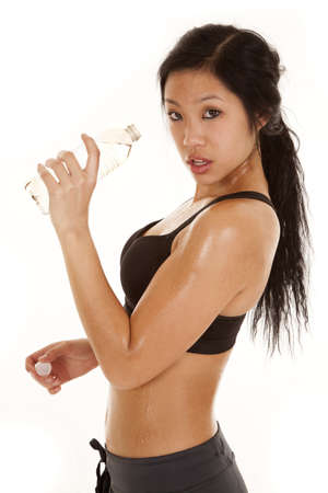 A woman getting ready to take a drink from her water bottle after a workout. photo