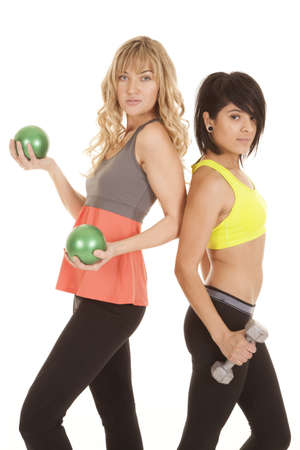 weighted: Two women working out one is lifting weighted balls the other weights.