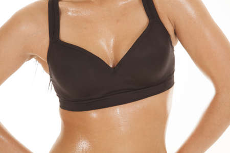 woman bra: A close up of a womans chest and stomach with sweat dripping off of it.