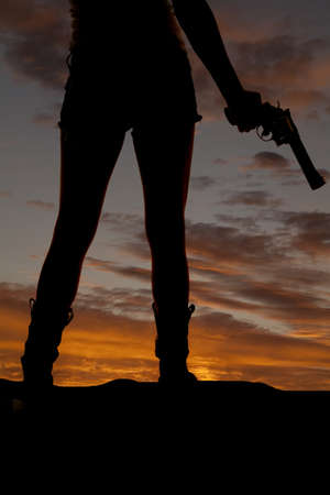 a silhouette of a woman holding on to a pistol in a beautiful sunset. photo