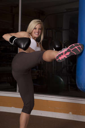 a woman working out with her kick boxing with an intense expression on her face. photo