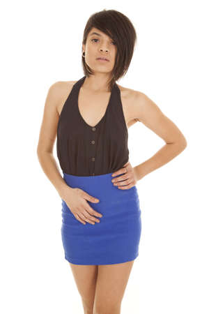 A woman with a sensual expression in her black tank and blue skirt.